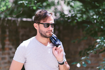 Casual young man outdoors,l with a cigarette Stock Photo