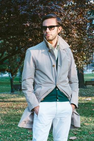 bel homme: Bel homme portant un manteau de tranchée dans le parc Banque d'images