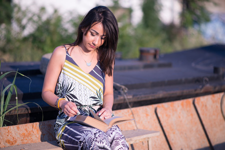 Beautiful brunette outdoors reading a book Stock Photo