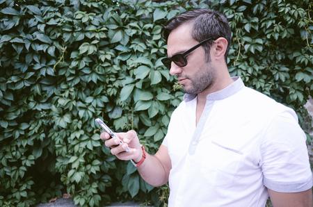gafas de sol: Hombre hermoso que mira su teléfono móvil, mensajes de texto