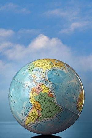 parallel world: globe against cloudy sky Stock Photo