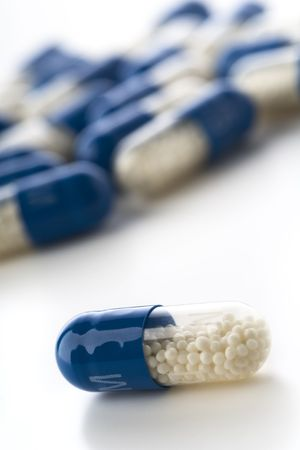 granules: blue capsules filled with granules on white Stock Photo