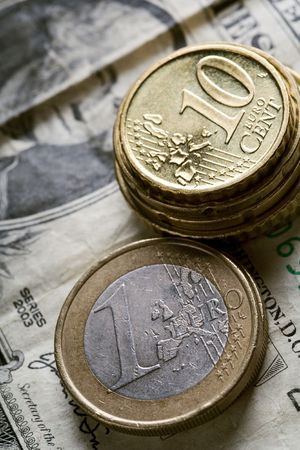 decreased: euro coins on a  dollar bill - decreased value of american currency