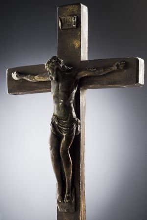 an old, broken crucifix against gray background photo
