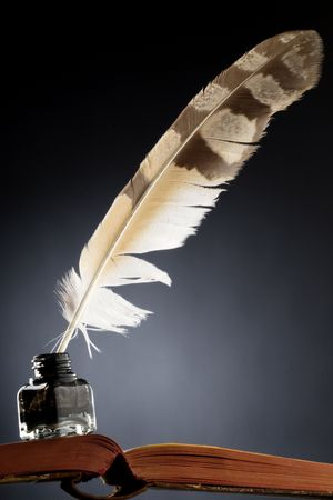 a feather quill in an ink bottle on an open book Stock Photo