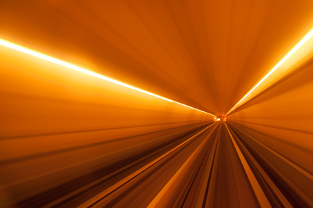 streight: Streight underground tunnel with orange light and rail Stock Photo