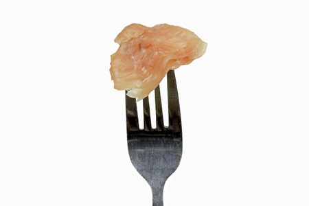 raw chicken on the fork on the white background