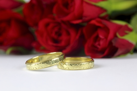 wedding rings and roses on the white background Stock Photo
