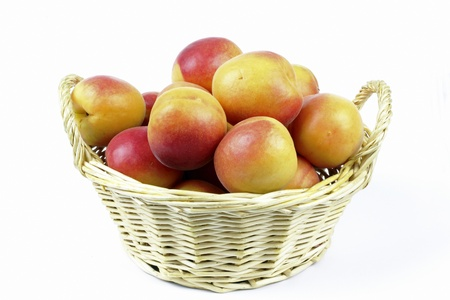 apricots in the basket on the white background Stock Photo