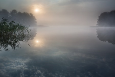 Beautiful sunrise over lake with reflections in water photo