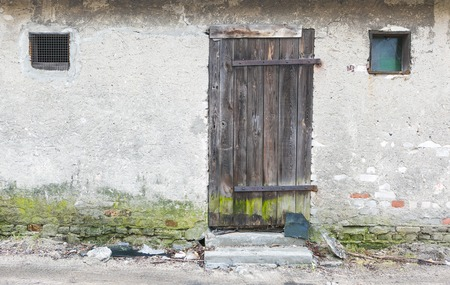Wall of old abandoned building with wooden doors photo