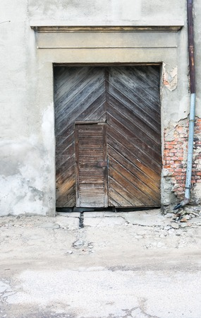 Wall of old abandoned building with wooden doors