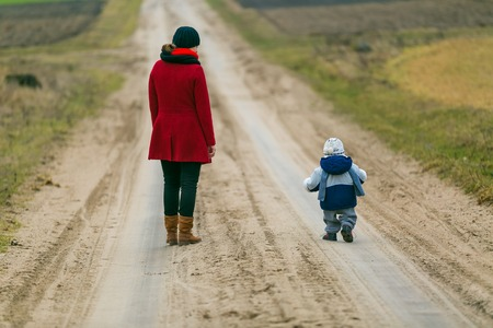 Mother with child walking by rural sandy road
