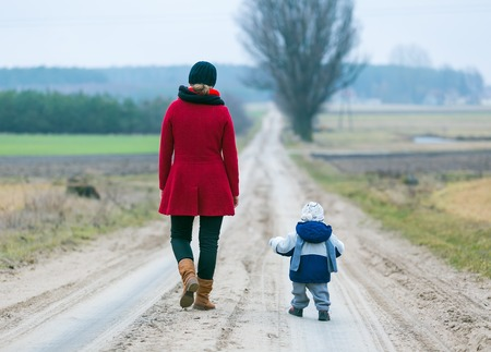 Mother with child walking by rural sandy road photo