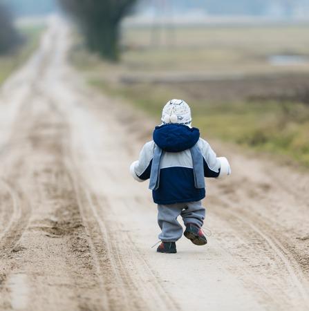 Little child walking self by rural sandy road