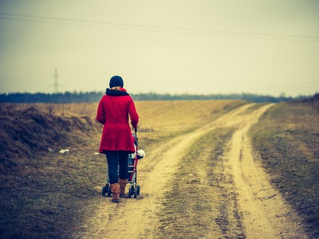 lomography: Vintage photo of woman walking by sandy road with stroller Stock Photo