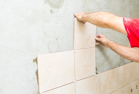 construction mason man hands on tiles work with cement mortar photo