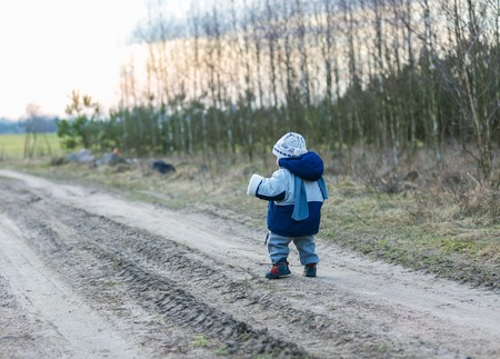 Little child walking self by rural sandy road photo