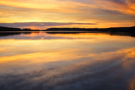 Beautiful calm lake with reflections in water photographed in sunset light photo