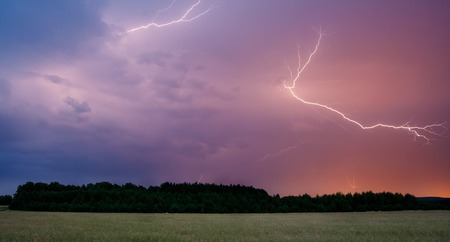 Thunderbolt over cereal field at summer time storm photo