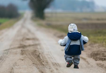 peuter kind lopen door landelijke zandweg in het vroege voorjaar Stockfoto