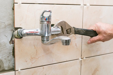 Plumber hand fixing water tap with spanner photo