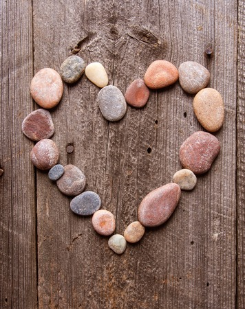 small stones heart shape on wooden old table