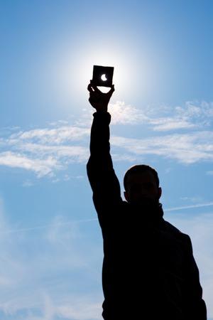Gedeeltelijke verduistering van de Zon. Man die een sterk zonlicht door donkere plaat en laat de zon eclips. man de hand silhouet op blauwe hemel. Stockfoto