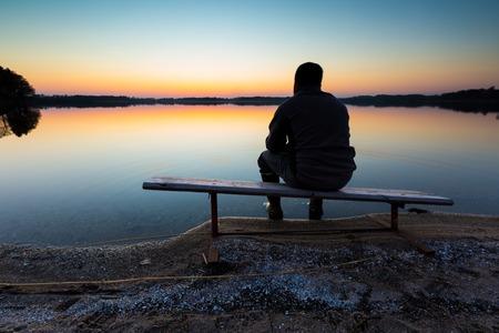 Bank op oever van het meer bij zonsondergang. Mooi landschap met een man zitten en kijken op zonsondergang. Gefotografeerd in Polen.