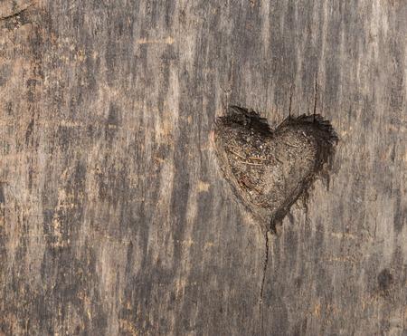 Kleine hartvorm gesneden in oud hout. Beeld nuttig als achtergrond Stockfoto