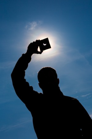 Partial Sun eclipse. Man covering a strong sunlight by dark plate and shows sun eclipse. man hand silhouette on blue sky. photo
