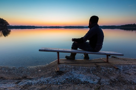 Man in lake water at sunset. Beautiful sunset with man silhouette photo