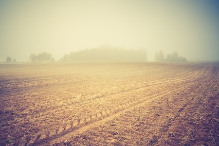 cloud industry: Sad autumnal landscape with plowed fields. Photo with vintage mood effect