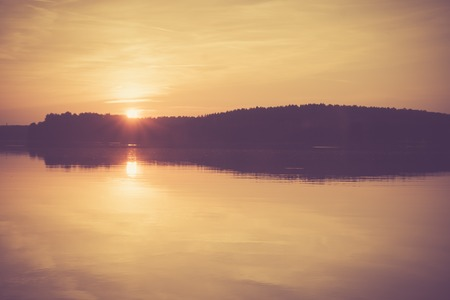 Beautiful landscape of sunset over lake. Photo with vintage mood. Photographed near Olsztyn in Mazury lake district in Poland