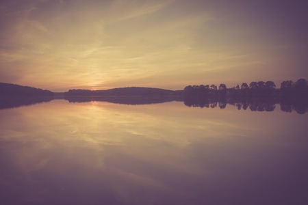 warmia: Beautiful landscape of sunset over lake. Photo with vintage mood. Photographed near Olsztyn in Mazury lake district in Poland