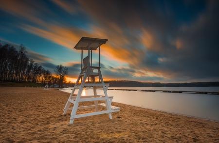 Lake landscape with lifeguard hut. Long exposure photo with dramatic sky. Polish lake beach on Mazury lake district. photo