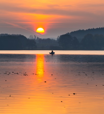 Beautiful lake landscape with fisherman boat and sunset sky. Typical polish lake in Mazury lake district. Orange sky and clouds reflected in water. Zdjęcie Seryjne - 37946516