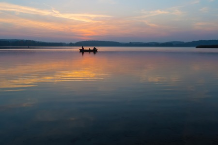 mazury: Beautiful lake sunrise with sky reflections in water. Tranquil colorful scene of typical polish lake in Mazury lake district. Stock Photo