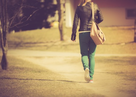 Young girl in green trousers walking by path in city. Photographed from behind