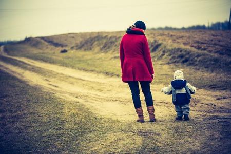 Moeder met kind lopen door landelijke zandweg. Platteland onder bewolkte hemel, foto met uitstekende stemming.
