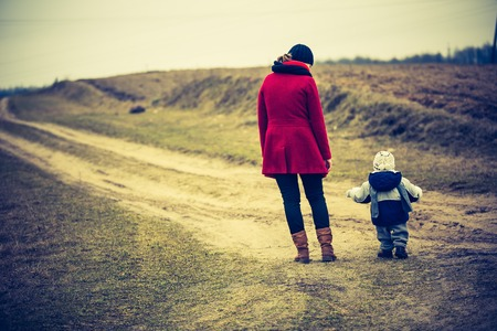 Mother with child walking by rural sandy road. Countryside under cloudy sky, photo with vintage mood. Standard-Bild