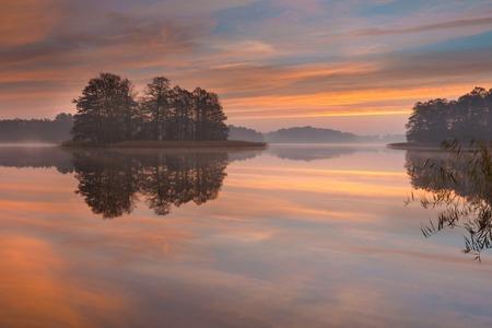 Beautiful sunrise over lake. Tranquil vibrant landscape with polish lake. photo
