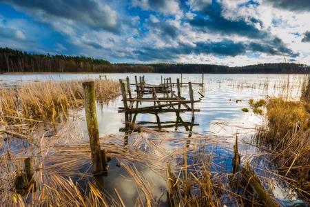 lake district: Small pier on lake, beautiful long exposure photo. Mazury lake district. Stock Photo