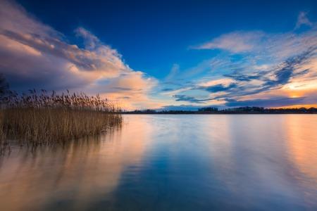 Mooie zonsondergang over kalm meer. Kleurrijke en levendige landschap van de oever van het meer met riet. Rustig landschap nuttig als achtergrond Stockfoto