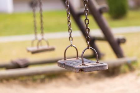 niños en recreo: Columpio vacío en el parque infantil en la ciudad. Foto de archivo