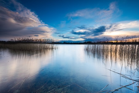 long lake: Beautiful sunset over calm lake in Mazury lake district. After sunset sky reflecting in water, calm vibrant landscape. Stock Photo