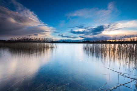 Mooie zonsondergang over kalm meer in Mazurië wijk meer. Na zonsondergang hemel weerspiegelt in het water, te kalmeren levendige landschap.