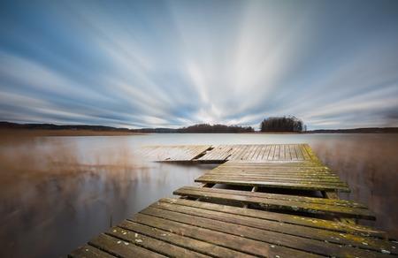 lake with jetty. long exposure landscape. Autumnal bad weather landscape photographed on polish lake. photo