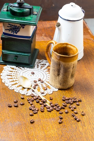 Coffee still life. Coffee grinder, coffee beans, jug and spoon on wooden table. Studio shot photo