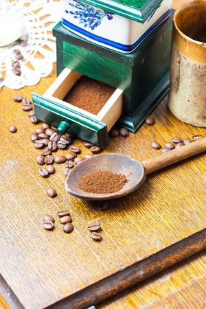 decaffeinated: Coffee still life. Coffee grinder, coffee beans, jug and spoon on wooden table. Studio shot